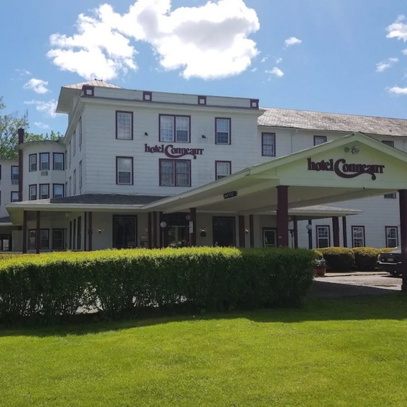 Hotel Conneaut fouls inspection; Ice machine, a food contact surface, was observed to have black residue, several small flying insects in bar area around soda dispensers