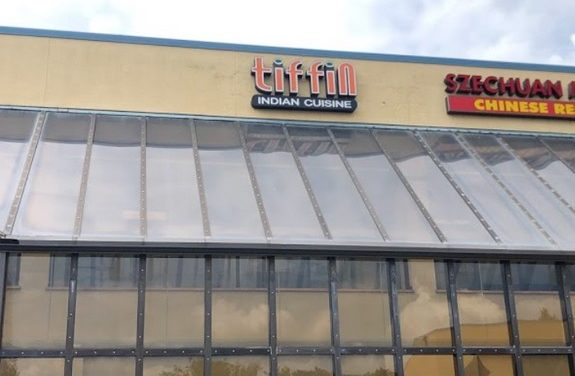 20 violations Tiffin Indian Cuisine in Elkins Park; Rodent-like droppings observed in dry storage room on floor and on lemonade bottle on storage shelf, Employee personal food plate stored on cook's line prep refrigerator cutting board